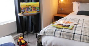 Family hotel room at The Red Lion, Odiham with children's books and toy box on the bed